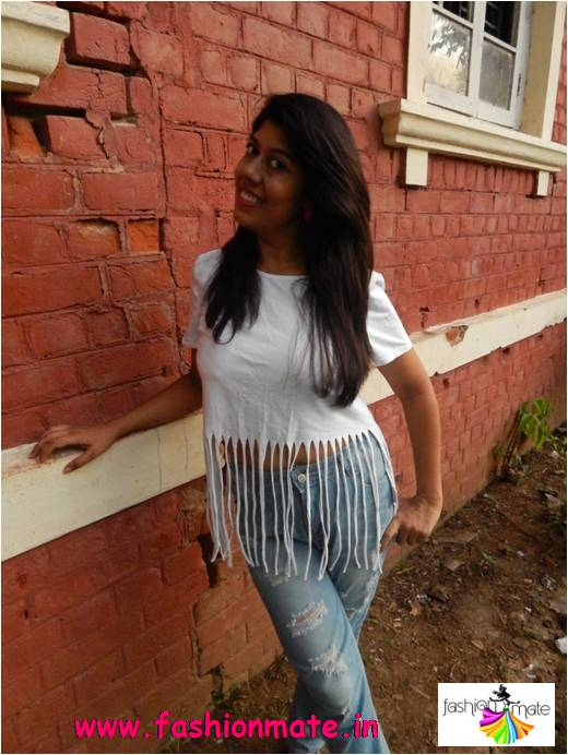 Style your ripped denims in bohemian way with fringed top